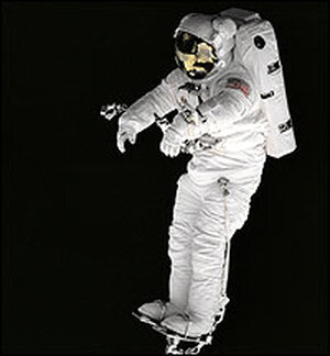 Against the blackness of space, mission specialist Peter J.K. Wisoff stands on a robot arm.