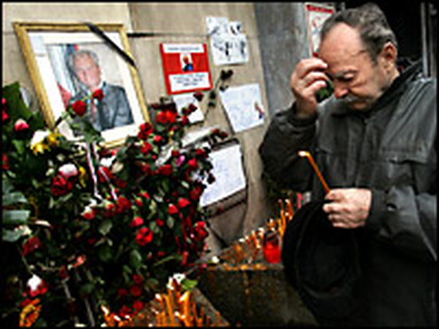 An elderly supporter of former Yugoslav president Slobodan Milosevic makes the sign of the cross on Monday as dozens of hardcore loyalists waited in line in the snow to pay tribute to their late idol in front of his party seat in central Belgrade.