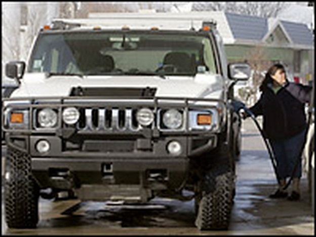 A motorist pumps gas into her Hummer in Illinois. The government is considering creating fuel economy standards for vehicles like the Hummer H2.