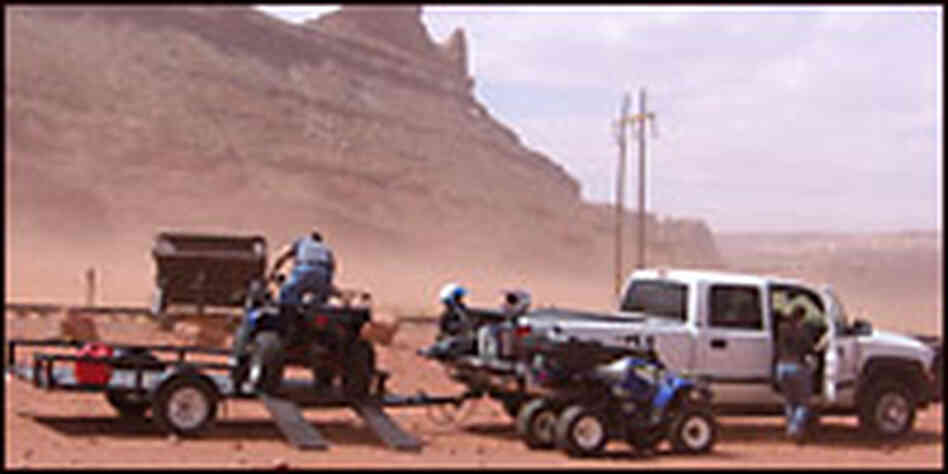 People preparing to ride an ATV in the desert. Credit: Richard Harris, NPR.