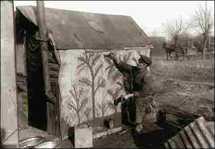 A soldier took the time to paint trees on canvas-like material covering the side of his hut.
