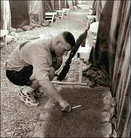 Army Warrant Officer Brook Turner trimming grass in Iraq.