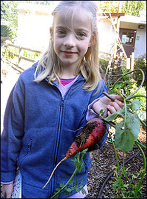 Third-grader Devina Boughton holds a carrot harvested from her school's garden.