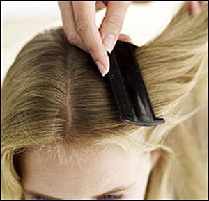 A woman combs a girl's hair.