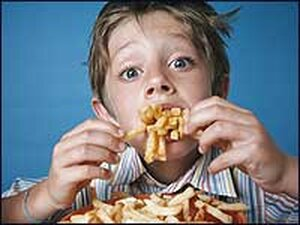 A boy eating French fries.