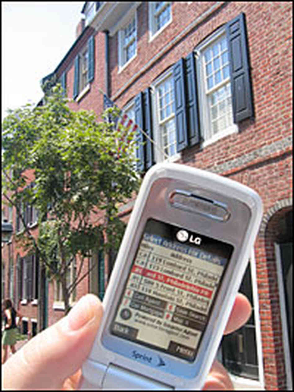 A phone displays GPS coordinates for homes in Philadephia, PA