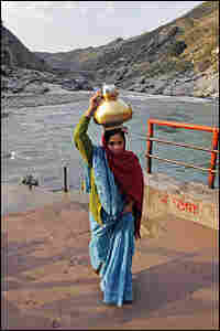 Each morning, women gather holy water from the Ganges in brass pots.