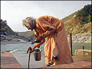 A woman collects water at one of the ghats, or steps, down to the shore of the Ganges.