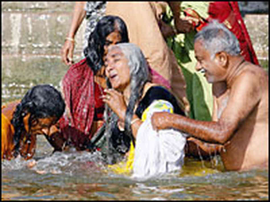 Hindu pilgrims bathe in the holy waters of the Ganges at Varanasi