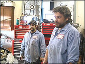Scott Beverly, co-owner of Flamingo Motors stands in a garage with his employee, Chad Bulger.