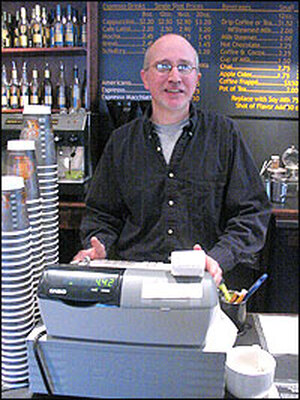 Paul Lovegreen stands behind the cash register at his coffee shop in Williamstown, MA.