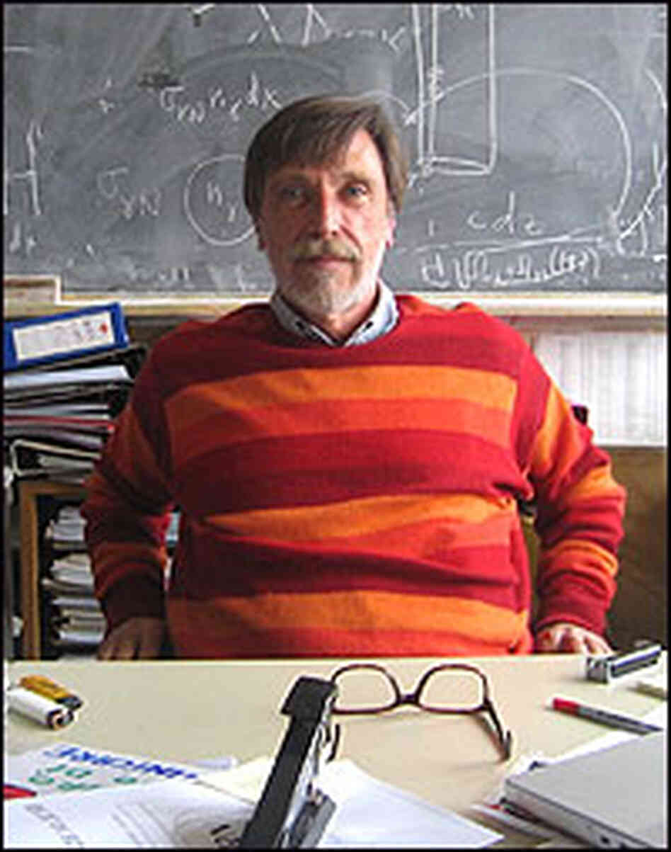 Physicist Alvaro De Rujula sits in his messy office in front of a blackboard.