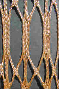 A detail of a braided tether.  Gold strings intricately interwoven.