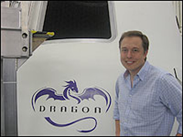 """Musk stands by a """"Dragon"""" capsule. He hopes to one day be able to carry seven people to orbit."""