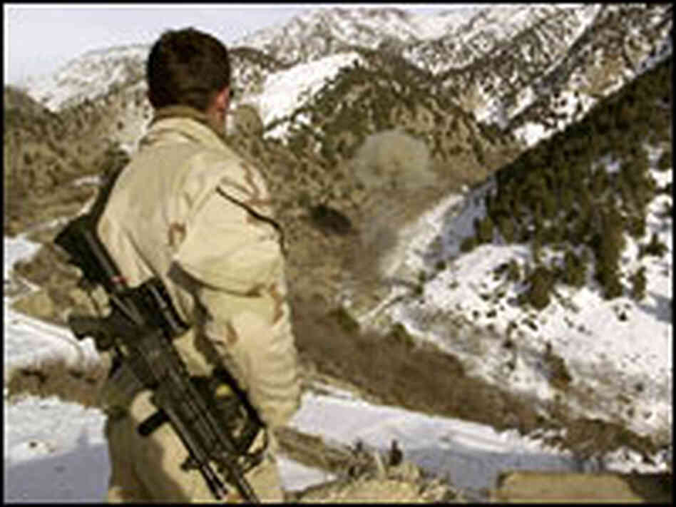 A Navy SEAL patrols an Afghan mountainside.
