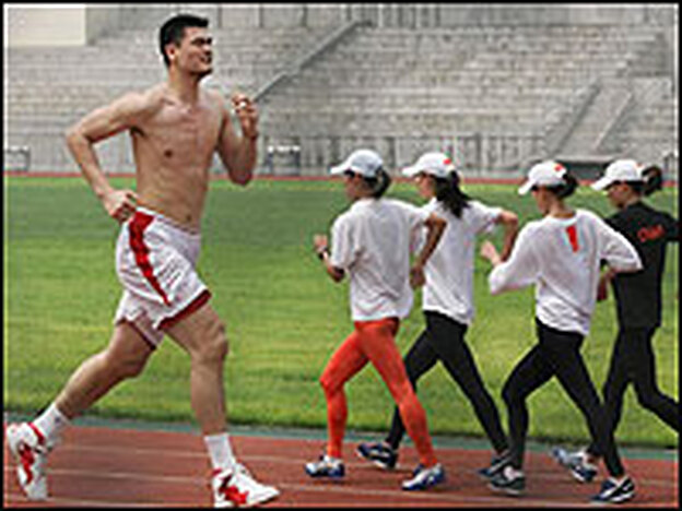 "At a looming 7'6"", Houston Rockets center Yao Ming runs around a track during a training session in Beijing in 2006."