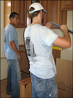 Volunteers Michael Chang (left) and Paul Clark work in the Booths' kitchen.