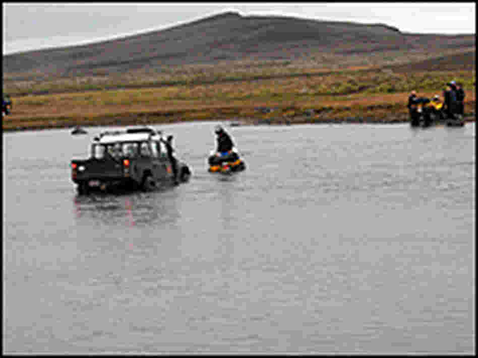An ATV driver attaches a chain to an expedition truck stuck in a river.