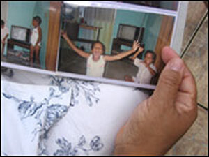 Angela Ramos-Michael holds a photo album with an old snapshot of her