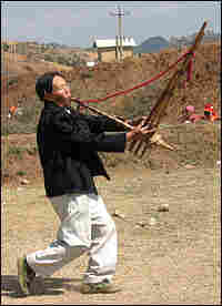 A man performs an elaborate dance as he plays a traditional Miao wind instrument called a lusheng.