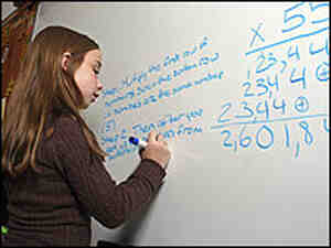 A girl works on a math problem.
