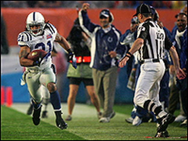 Indianapolis Colts' safety Bob Sanders returns a fourth-quarter interception as coach Tony Dungy raises a fist in triumph.