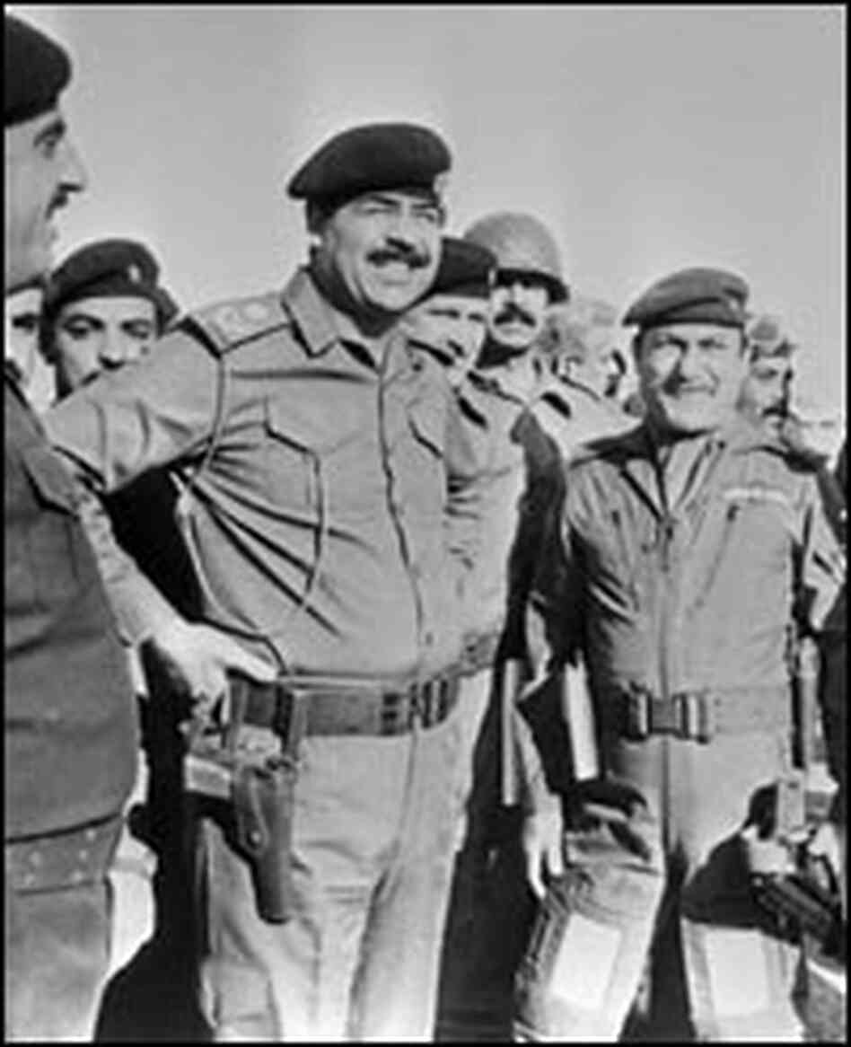Iraqi President Saddam Hussein confers with members of his staff during the Iran-Iraq war in 1987.