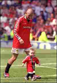 David Beckham, then of Manchester United, celebrates winning the championship with his son Brooklyn.