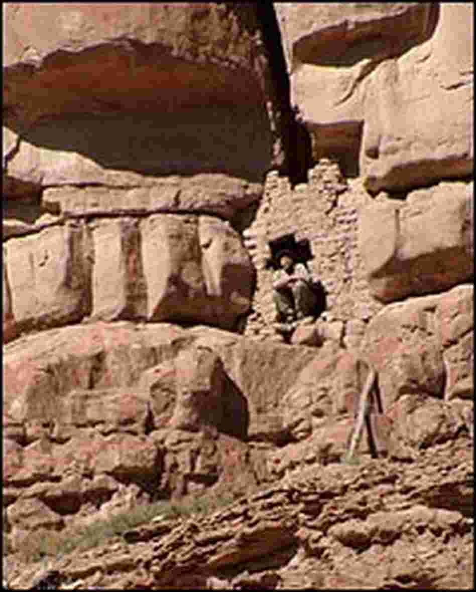 Craig Childs crouches in the doorway of a cliff dwelling.