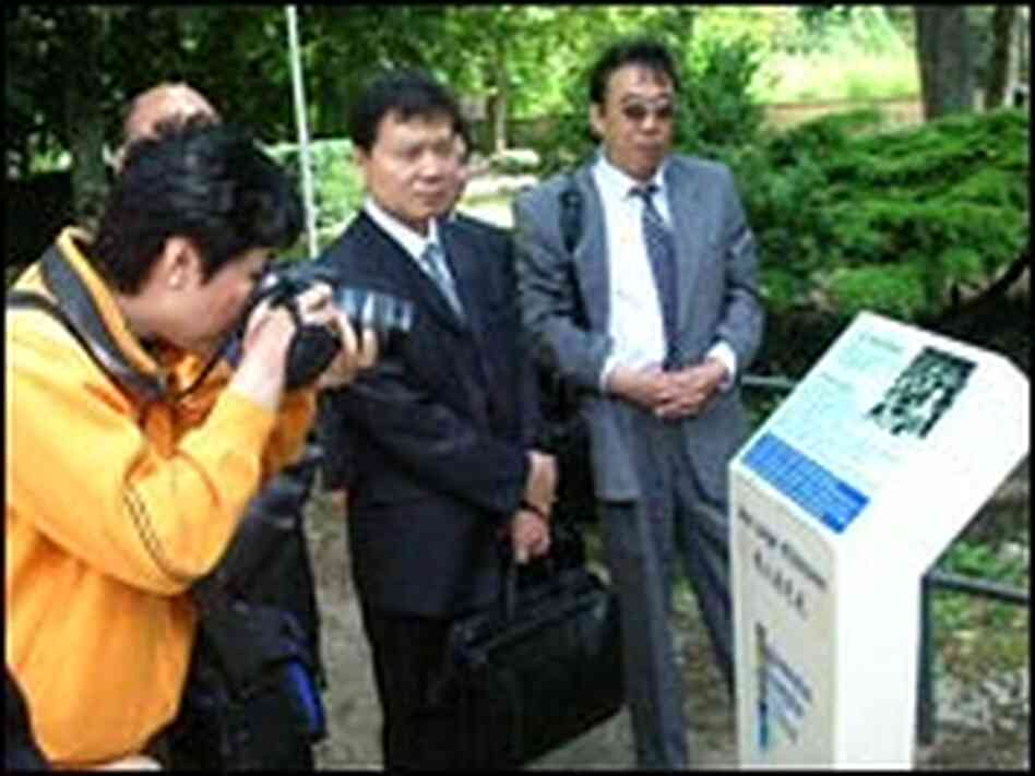 Chinese tourists visit a plaque in a park in Montargis, France.