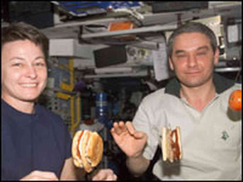 Astronaut Peggy Whitson and cosmonaut Valery Korzun eat aboard the International Space Station.