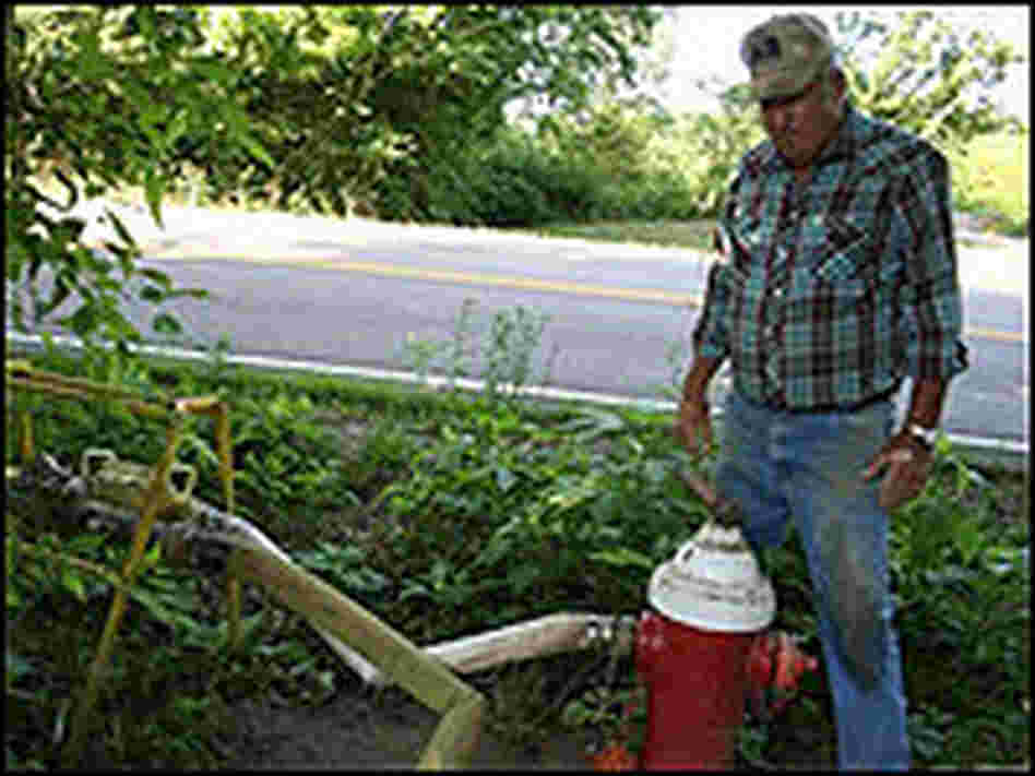 A farmer transfers water from a fire hydrant to the crops.