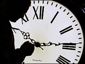 A worker adjusts a clock's hand on a Seth Thomas post clock at the Electric Time Company in Mass.