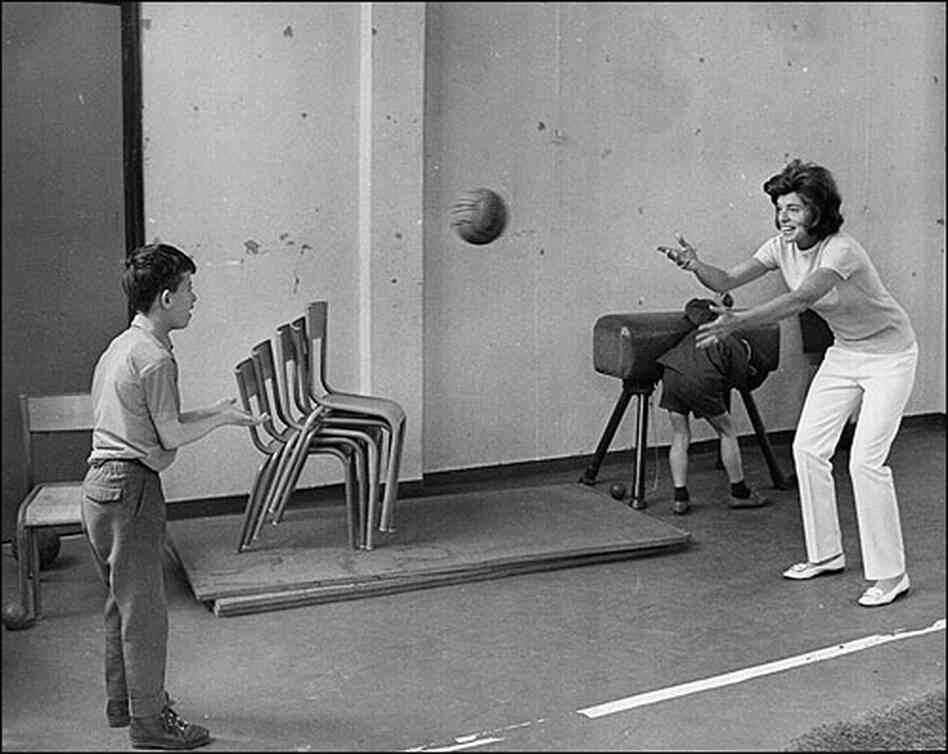Shriver and a child play catch in a Paris gymnasium in 1969.