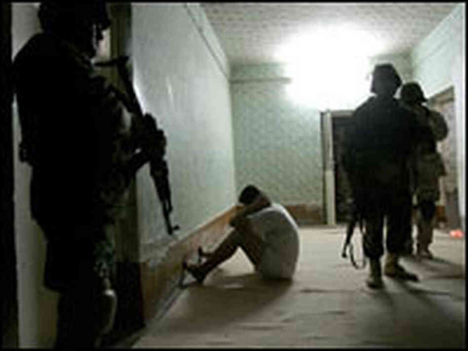 A temporarily detained Iraqi man sits facing a wall as Iraqi police search his house.