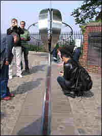 Tourists visit the prime meridian in Greenwich.