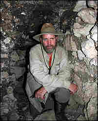 Dr. David Freidel stands in front of a looters tunnel