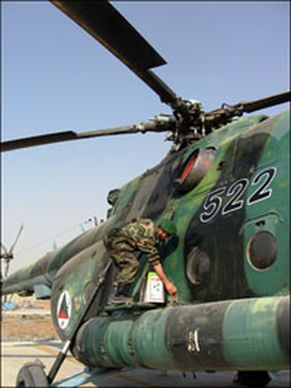 An Afghan enlisted man scrubs a helicopter with fuel to clean its hull of the country's rampant dust. Like parts and tools, cleaning agents are hard to come by for Afghanistan's air corps.