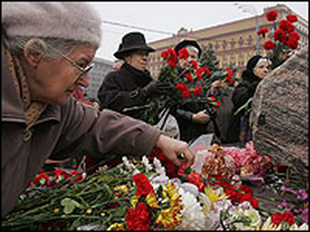 Members of the Memorial organization lay flowers and light candles at a monument commemorating the victims of Soviet repression.