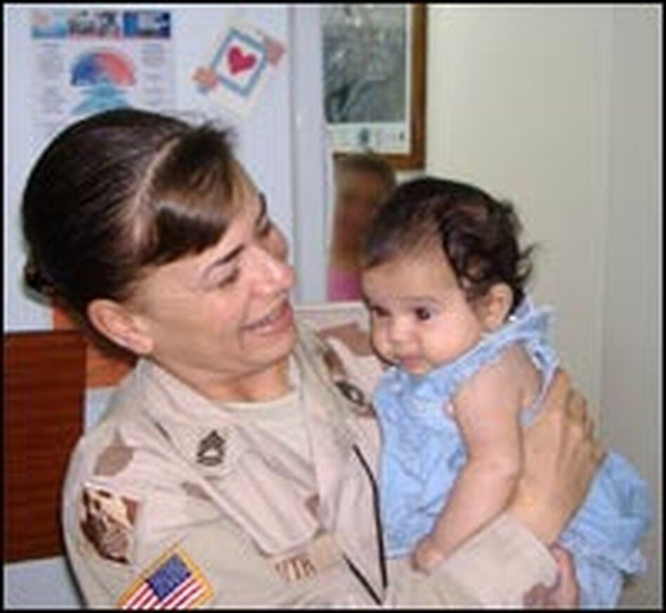 "Sgt. Kimber Smith holds an infant brought into her office in Iraq last year. ""For a brief moment, I felt normal,"" she says."
