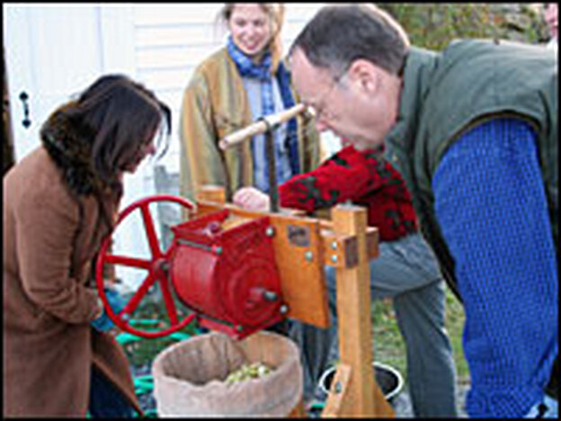 Renee Montagne and Kimball press apples to make cider for Kimball's cider gravy recipe.