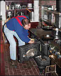 Kimball bakes a pie in the reconditioned Olds and Whipple stove in his farmhouse kitchen.