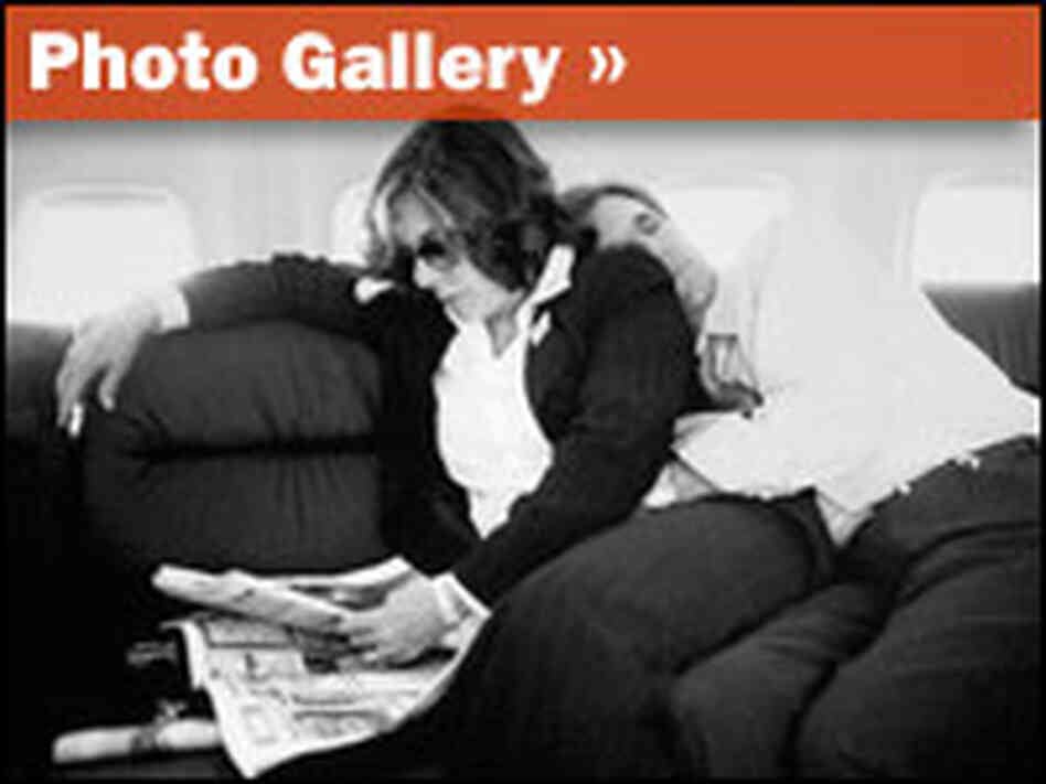 Sen. John Kerry naps aboard a plane as his wife Teresa Heinz Kerry reads a newspaper.