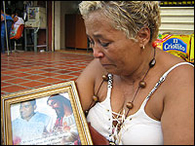 Mercedes Eloisa Caraballo holds a picture of her son who was recently murdered by gang members in the poor Caracas neighborhood, El Valle.  The neighborhood is a hotbed of drug trafficking and drug gangs.