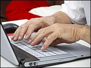 hands typing on a laptop computer.
