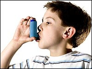 A boy using an asthma medicine inhaler.
