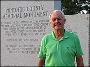 American Legion Post Commander Bill Wardlaw stands in front of a granite war memorial in Pontotoc.