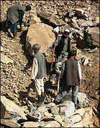 Villagers build a new road across a mountain.