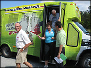 """Prospective home buyers file off of real estate agent Marc Joseph's """"Foreclosure Tours R Us"""" bus"""
