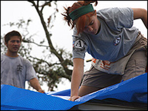 A young woman securing a blue tarp to protect a home.